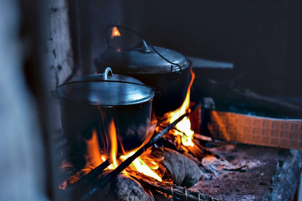 Two cast iron dutch ovens with lids sitting on a fire