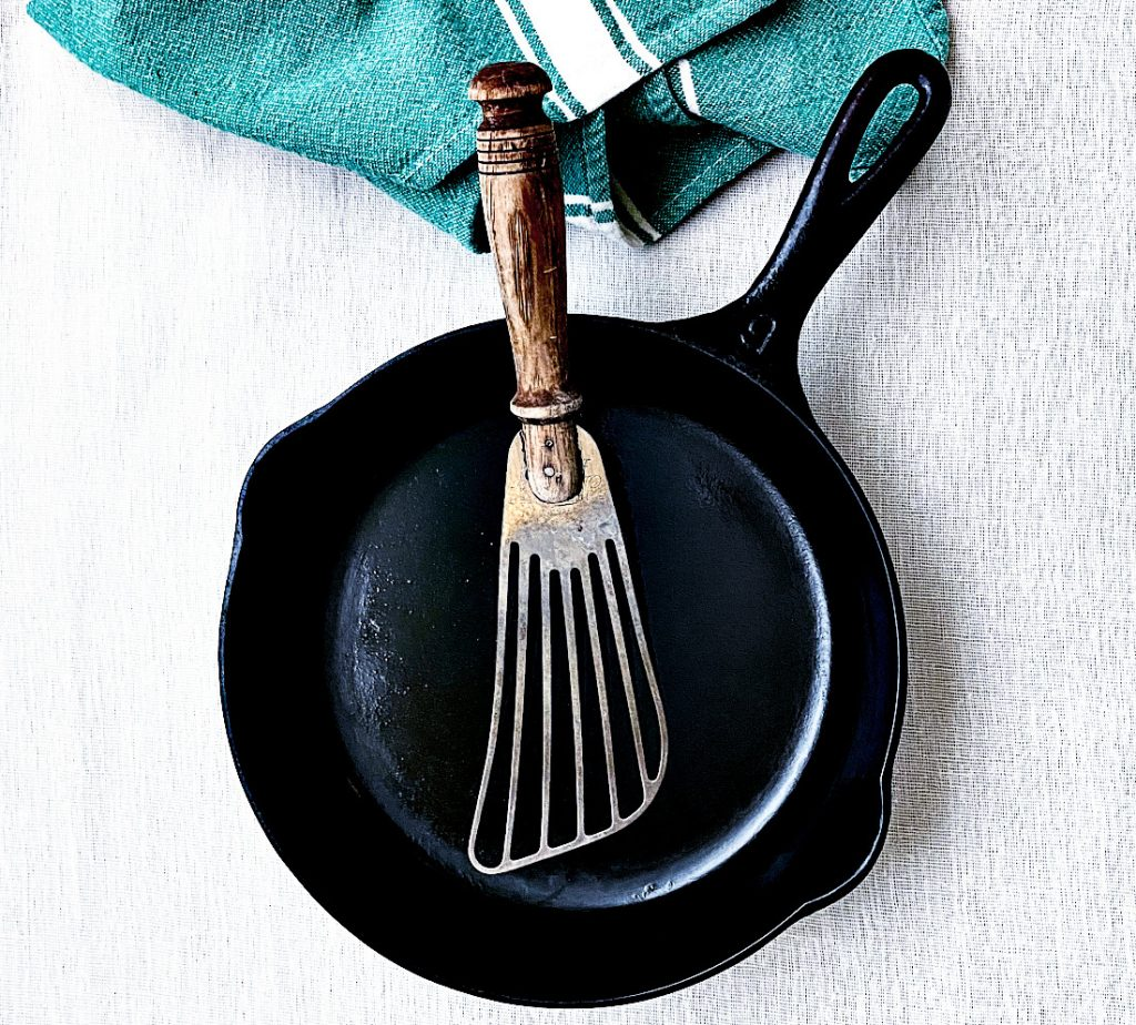 A Metal utensil resting in a cast iron pan