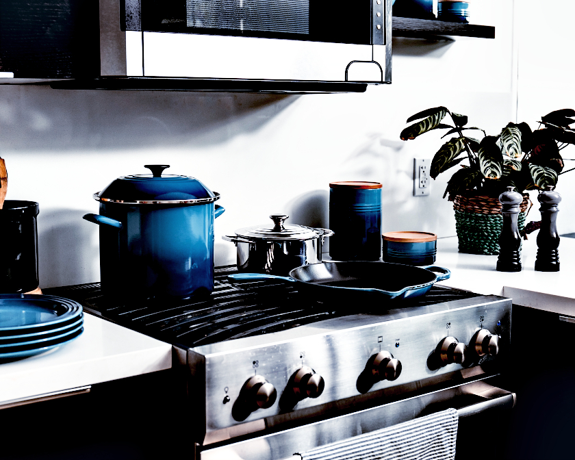 Ceramic cookware and a stainless steel pan on gas stove