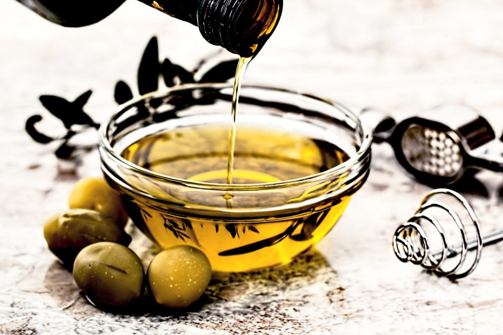 Olive oil in a bowl with olives next to it