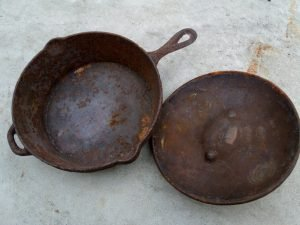 A rusted cast iron skillet with its lid