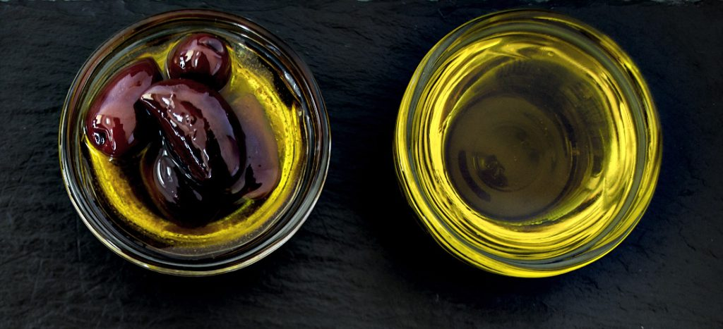Olive Oil in two small bowls, one with olives