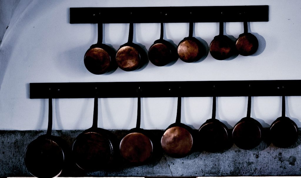 Copper skillets lined up on wall.