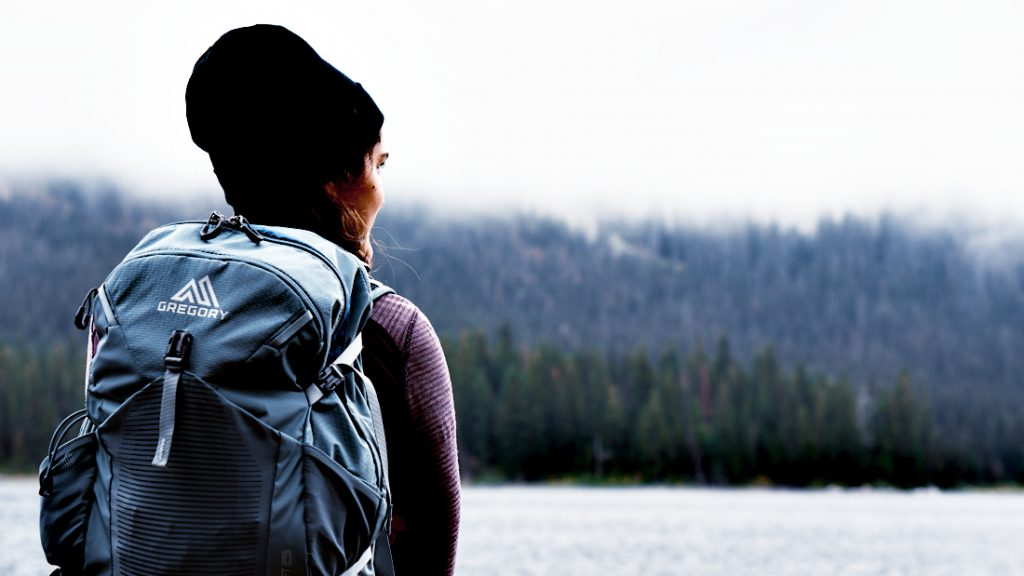 Backpacker with a small, light, backpack looking over the like