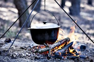 A cast iron dutch oven being hung over a campfire by its loop handle. Best Dutch Oven for Camping - Featured Image