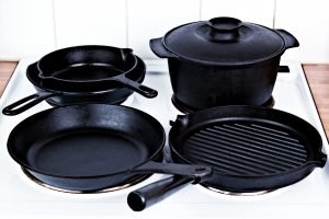 One large cast iron skillet, two nested smaller cast iron skillets, one cast iron dutch oven and one cast iron grill pan all sitting on a stove top. Best Cast Iron Cookware Sets Featured Image
