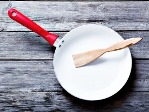 White and red ceramic pan with a wooden utensil. Best Non Stick Pan Without Teflon - Featured Image
