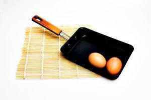 A rectangular tamagoyaki pan with two whole uncooked eggs - best tamagoyaki pan featured image