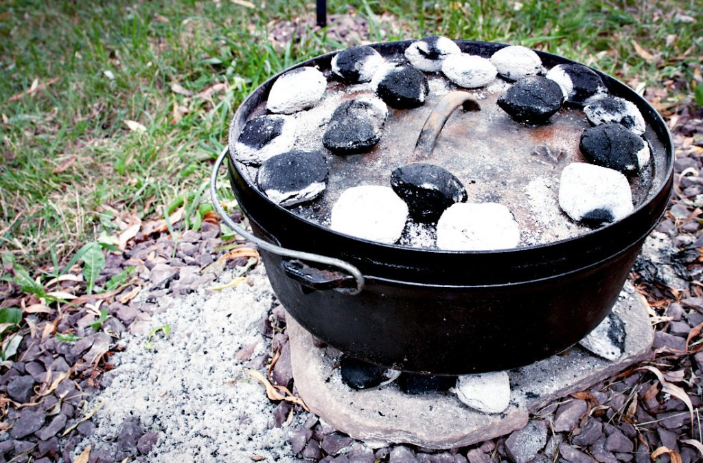 Cooking dinner in the dutch oven using charcoals placed underneath and on the flat lid to heat it