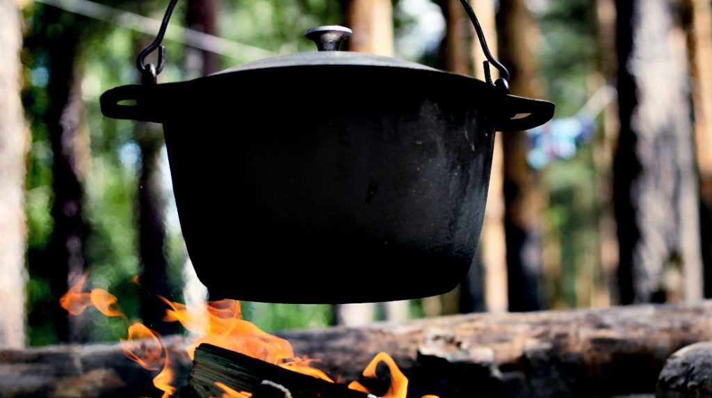 A Cast Iron Dutch Oven hanging over a campfire