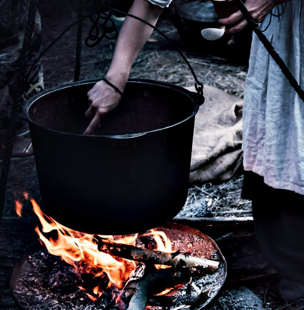 A Dutch oven hanging from a looping wire handle over a campfire.