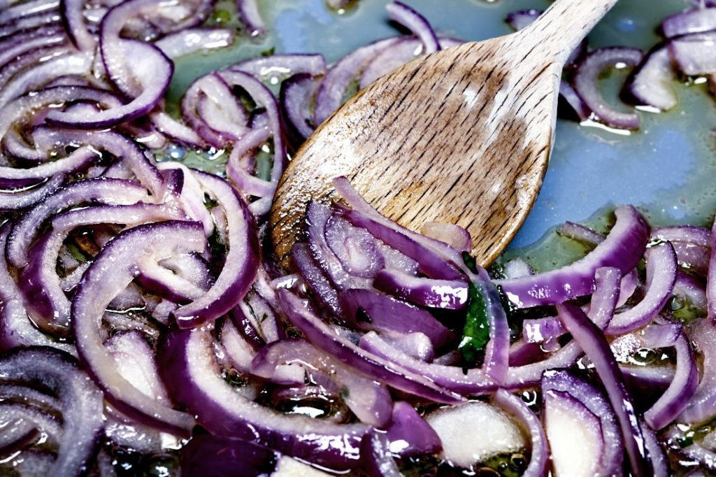 Stirring sauteing red onions with wooden spoon in cooking pan, closeup