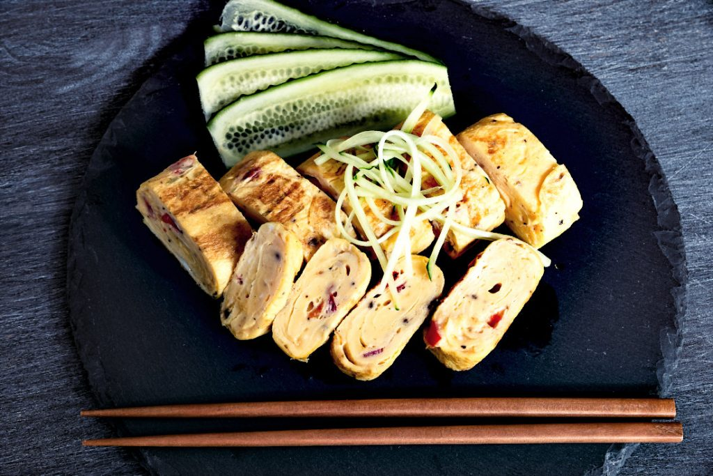 Traditional Japanese rolled omelette Tamagoyaki and sliced cucumber on a black slate board with chopsticks, top view