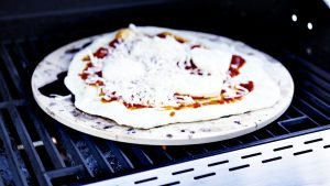 A handmade pizza sitting on a pizza stone, itself resting on an outdoor gas grill. Featured Image Best Pizza Stone For Grills