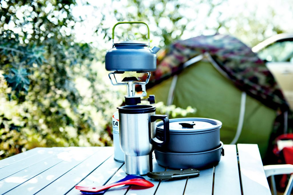 A camping kettle on a burner next to a thermos and some nested camping cookware.