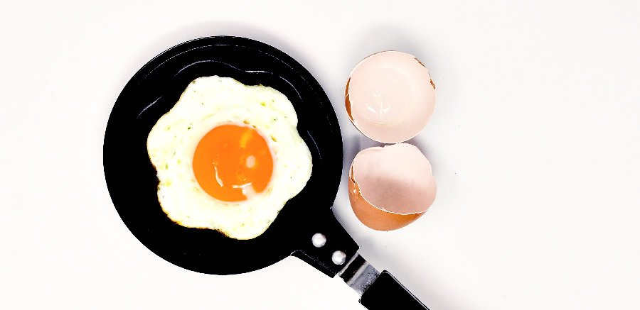An egg being fried in a star shape in a non stick pan