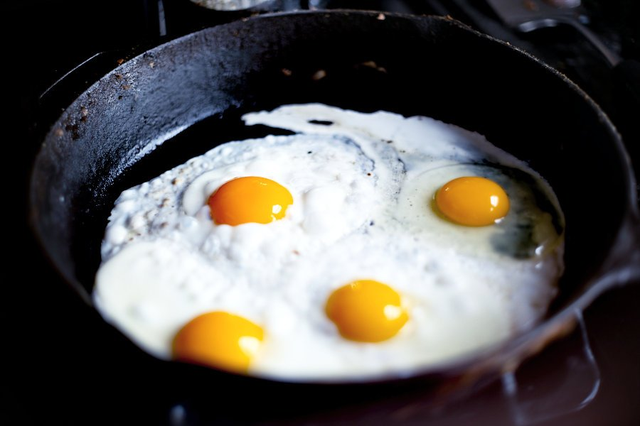 Four eggs being fried in one pan