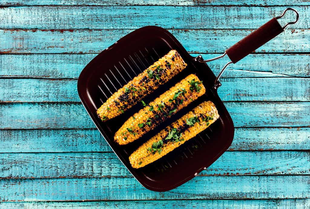 A Grill Pan with 3 cobs of corn