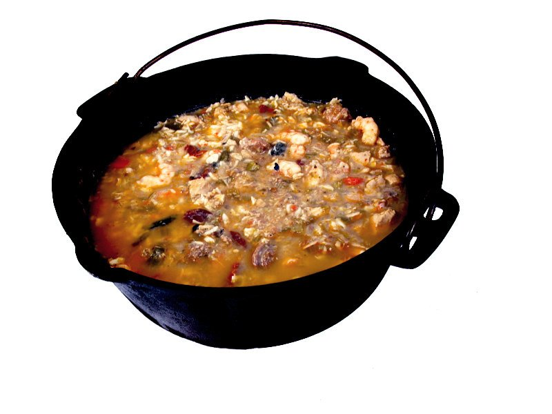a cast iron pot of seafood gumbo on a white background