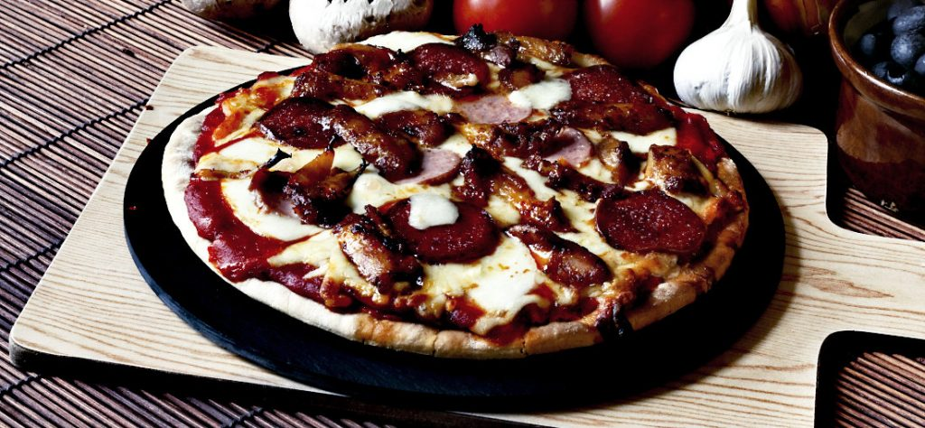 Barbecue meat feast pizza with a topping of pepperoni, sausage, salami and chicken wings sitting on a pizza stone.