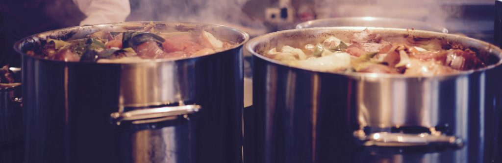 Two tall stainless steel stockpots cooking stew