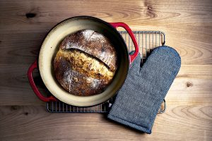 An enameled cast iron Dutch oven with a loaf of bread inside and some oven gloves next to it - best Dutch oven for baking bread