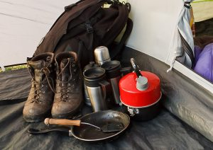 Interior view of a dome tent set up for camping with various equipment and sleeping bag inside inner compartment - Best Backpacking Fry Pan Featured Image