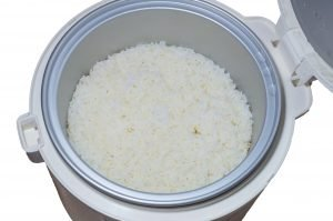 Stream rice in electric rice cooker on white background - Best Sushi Rice Cooker