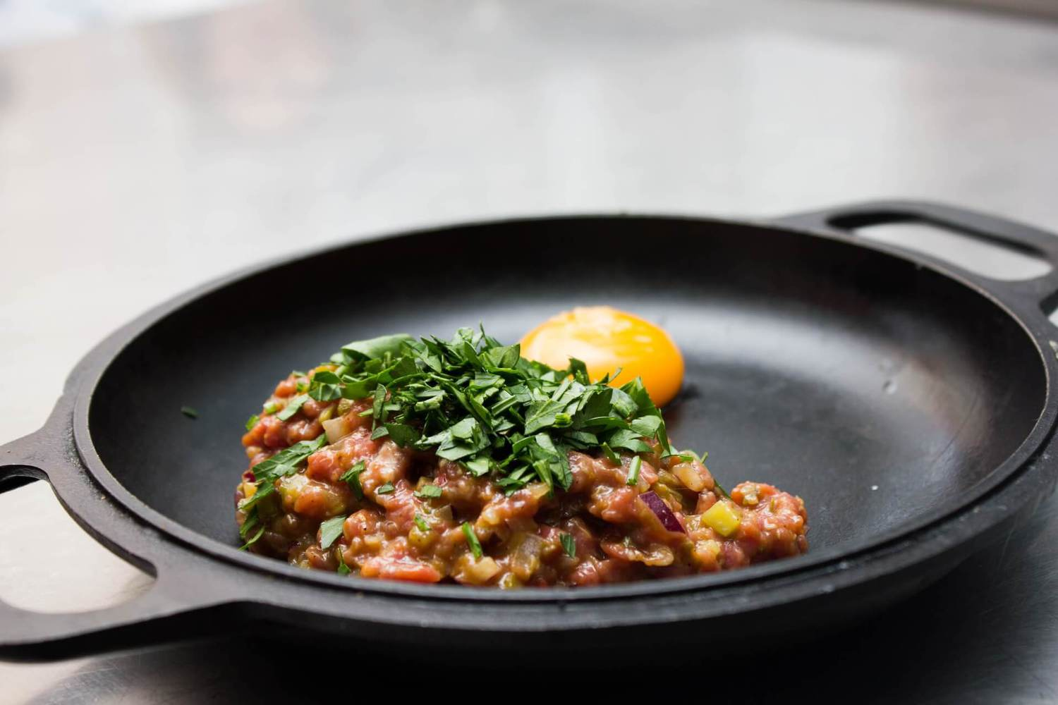 a stir fry and an egg cooking on a black griddle
